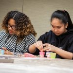 Ariyah Powers, left, and Dabria Arana from West Side STEM Magnet Middle School in Groton, Connecticut, use strawberries to learn how to extract DNA. (Christopher LaRosa/UConn Photo)