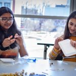 Dhanya Chasmawala, left, and Julia Alkhayer from Timothy Edwards Middle School in South Windsor, Connecticut, use simple materials to learn about Newton's Law of Motion. (Christopher LaRosa/UConn Photo)