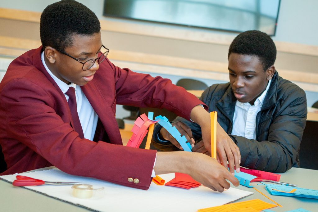 Devonte Daley, left, and Keenon Christian from Jumoke Academy in Hartford learn about Newton's Laws of Motion by building and testing a balloon-powered rocket car from simple materials. (Christopher LaRosa/UConn Photo)