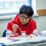 Isai Cevallos from Pulaski Middle School in New Britain learns how to extract DNA from strawberries to learn more about biomedical engineering. (Christopher LaRosa/UConn Photo)