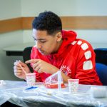 Elijah Black from West Side Middle School in Groton learns about biomedical engineering by learning the procedures to extract DNA from strawberries. (Christopher LaRosa/UConn Photo)