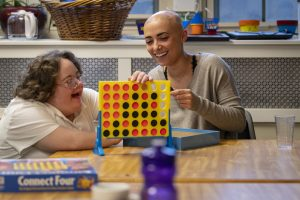 At right, Vanessa Rosa '19 (CLAS) and April play Connect Four in Sprague Residence Hall. Vanessa and April are part of the Best Buddies/STAAR program where undergraduate students are mentors to young adults with developmental disabilities. April 26, 2019. (Sean Flynn/UConn Photo)