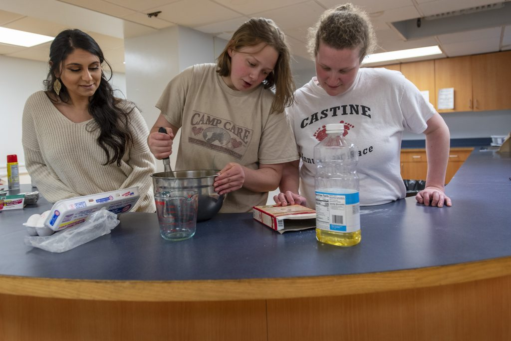 From left, Saira Khurana '19 (CLAS) assists Katie and Kate while making cupcakes in Sprague Residence Hall. (Sean Flynn/UConn Photo)