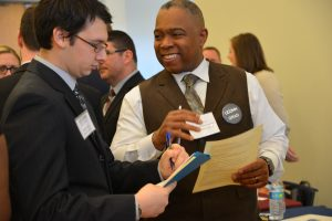 Samuel Galloway '01 6th Year, director of human resources at Bristol Public Schools, reviews a student's resume during the Education Career Fair. (Shawn Kornegay/Neag School)