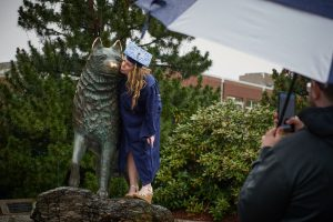Hannah Steinke gives the husky statue a kiss on the nose following College of Liberal Arts & Sciences commencement ceremony on May 12. (Peter Morenus/UConn Photo)