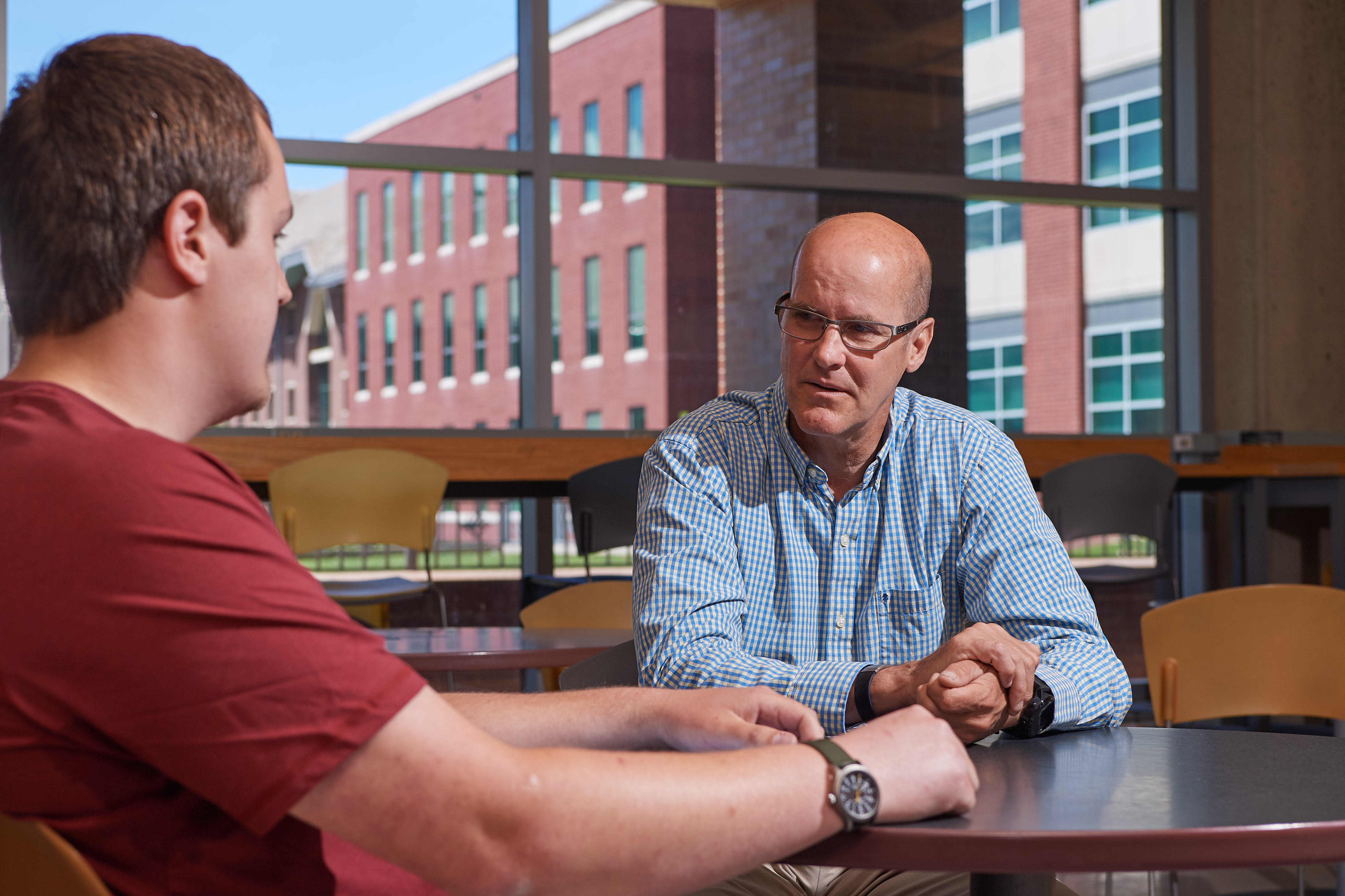 Joshua Bidwell '20 (CLAS) and Paul Hanlon, veteran and outreach coordinator for the Office of Veterans Affairs and Military Programs, meet at Bookworms Cafe at the Homer Babbidge Library. (Peter Morenus/UConn Photo)