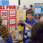 Alexander DeLuca, 10, displays how his invention 'Ez Pour' can aid disabled and elderly people in pouring their cereal in the morning. (Lucas Voghell '20 (CLAS)/UConn Photo)
