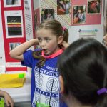Sawyer Montstream, 8, shows how her invention can help kids keep their sweatbands on. (Lucas Voghell '20 (CLAS)/UConn Photo)