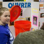 Payton Farrell, 8, shows off her device 'Ouvrir,' which can help people open buckets that have their lids on too tight. (Lucas Voghell '20 (CLAS)/UConn Photo)