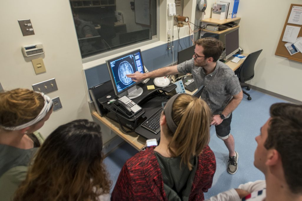 Charles Davis, a graduate student in psychology, shows an axial image of the brain to the group of local high school students. (Sean Flynn/UConn Photo)