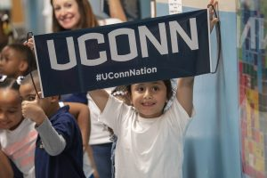 First-grader Emily Garcia holds up a UConn Nation banner during UConn Day at Kennelly School in Hartford on May 2, 2019. (Sean Flynn/UConn Photo)