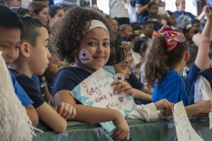Second-grader Juliet Cruz, facing the camera, is among the students of Kennelly School in Hartford, celebrating UConn Day along with her schoolmates, teachers, and UConn School of Education students on May 2, 2019. (Sean Flynn/UConn Photo)
