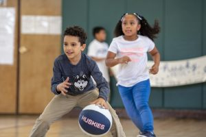 Third-grader Ediel Lopez-Torres, with the ball, and first-grader Stella Flores play basketball in a game against the teachers at Kennelly School on May 2, 2019. (Sean Flynn/UConn Photo)