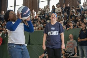 Third-grader Nathan Williams shoots the ball as math resource teacher Shannon Harrington looks on during a kids vs. teachers basketball game at Kennelly School, part of the school's UConn Day celebrations on May 2, 2019. (Sean Flynn/UConn Photo)