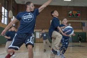 Third-grader Jonathan Rios charges the basket, as school social worker Nelson Veras '14 (CLAS), '18 MSW, attempts a block, during a basketball game of kids vs teachers at Kennelly School on May 2, 2019. (Sean Flynn/UConn Photo)