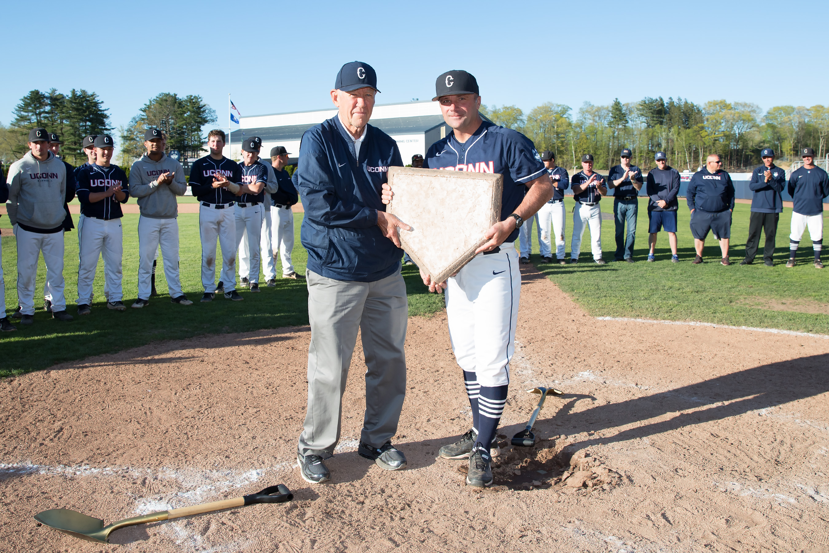 Jim Penders, right, accepts the home plate from Andy Baylock. (Stephen Slade/UConn Today)