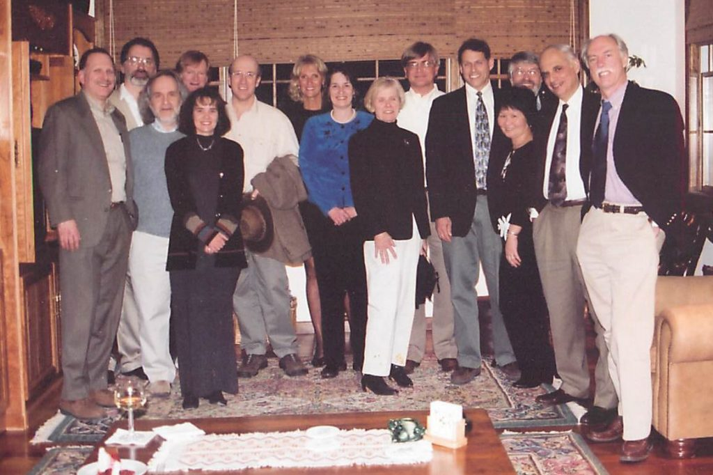 Group photo of 15, mostly UConn Health researchers, in a living room