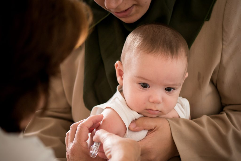 A doctor giving a baby an injection. (Getty Images)