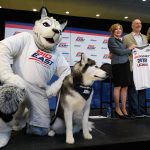 Jonathan the Husky, left, and Jonathan XIV pose for a photo, while President Susan Herbst, Joel Fisher of MSG, and Val Ackerman, commissioner of the Big East look on, following an event announcing UConn's return to the Big East athletic conference on June 27, 2019. (Peter Morenus/UConn Photo)