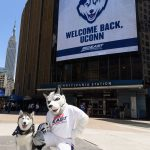 Jonathan the Husky and Jonathan XIV pose for a photo near a marquee welcoming UConn back to the Big East athletic conference outside Madison Square Garden on June 27, 2019. (Peter Morenus/UConn Photo)