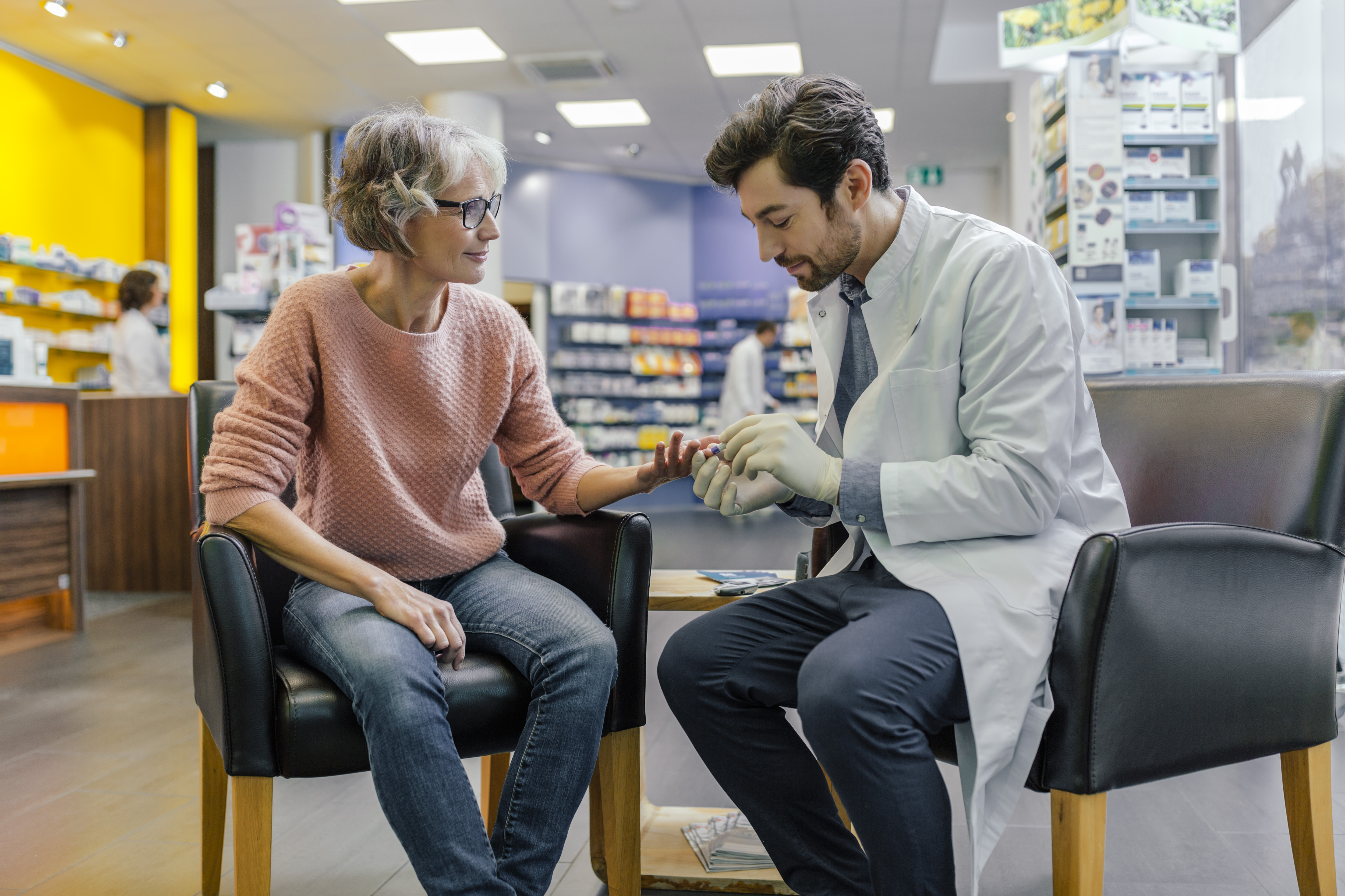 Pharmacist measuring blood sugar of customer in pharmacy. (Getty Images)
