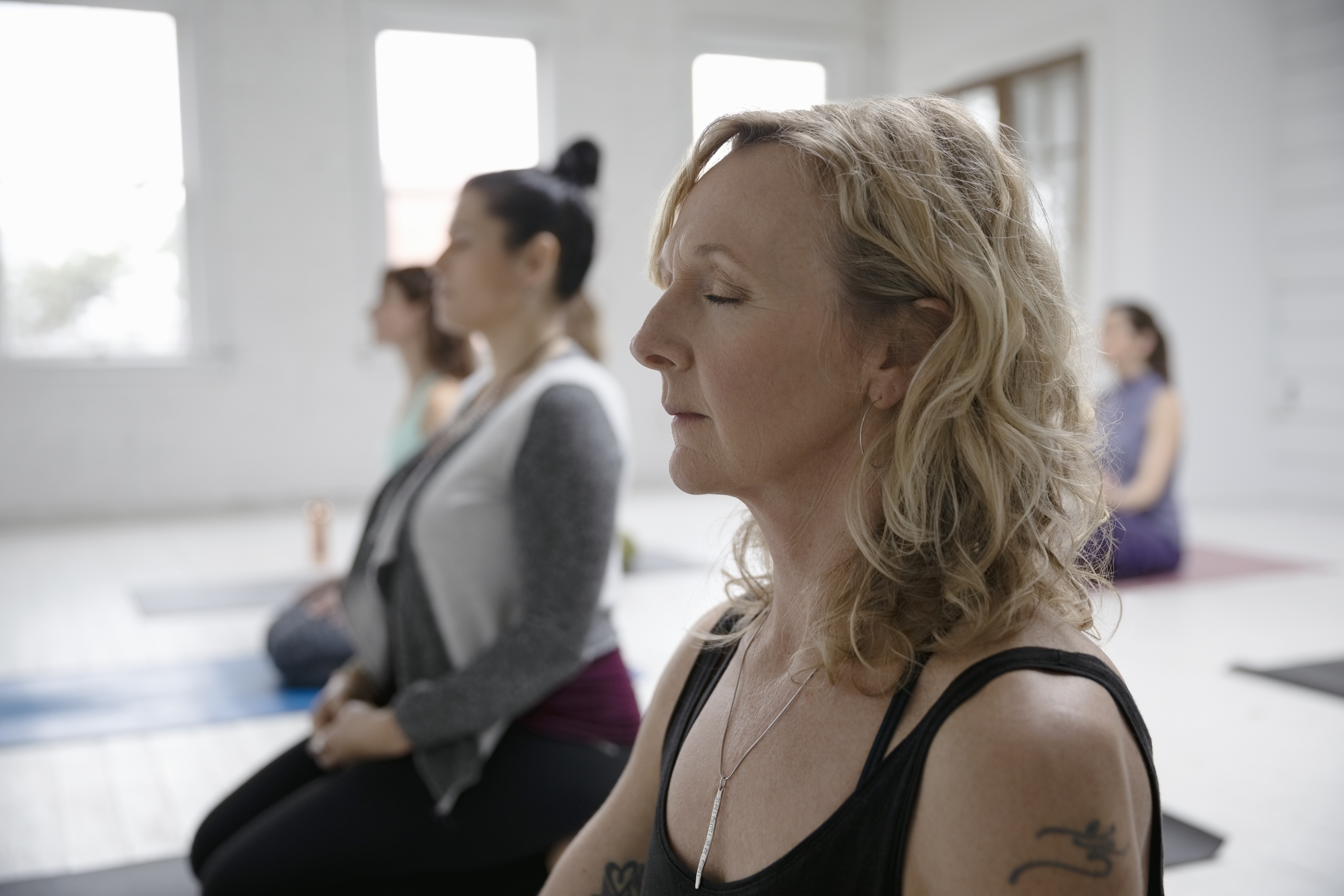 Serene woman meditating in yoga class. (Getty Images)