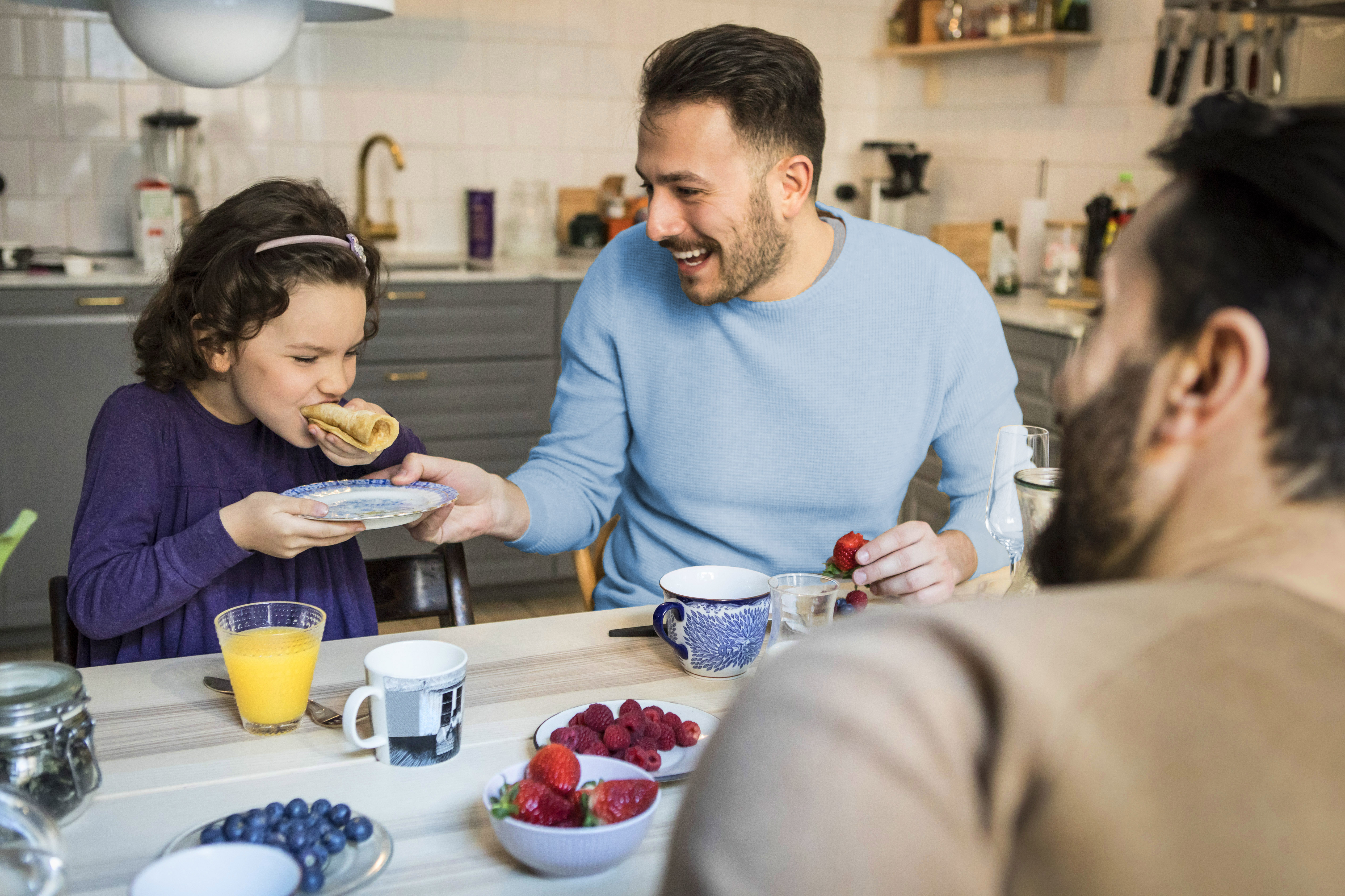 Laughing father holding plate while daughter eats pancake at table. (Maskot/Getty Images)