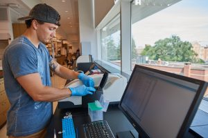 Ian Sands '20 (ENG) uses a device to characterize the size of nanoparticles in a lab at the Engineering Science Building on June 24, 2019. (Peter Morenus/UConn Photo)
