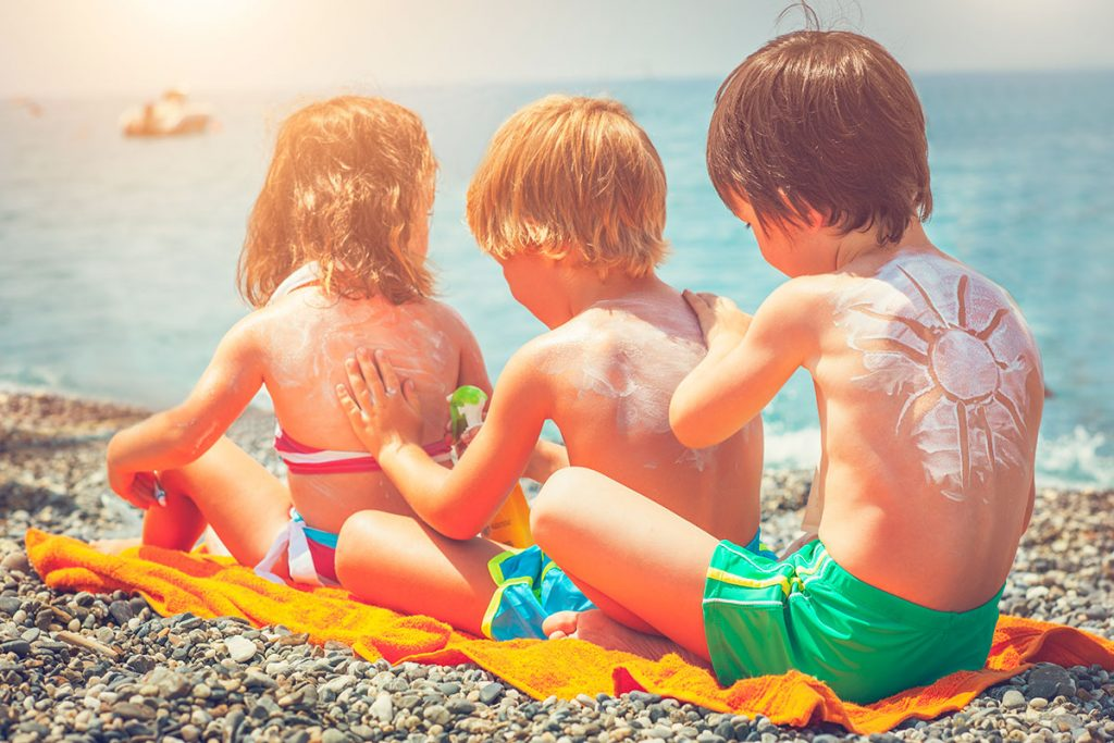 Three kids applying sunscreen to each other on the beach