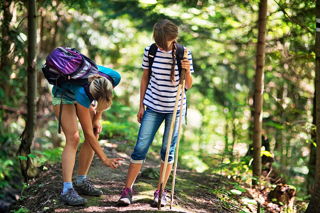 Mother spraying insect repellent on daughter in woods