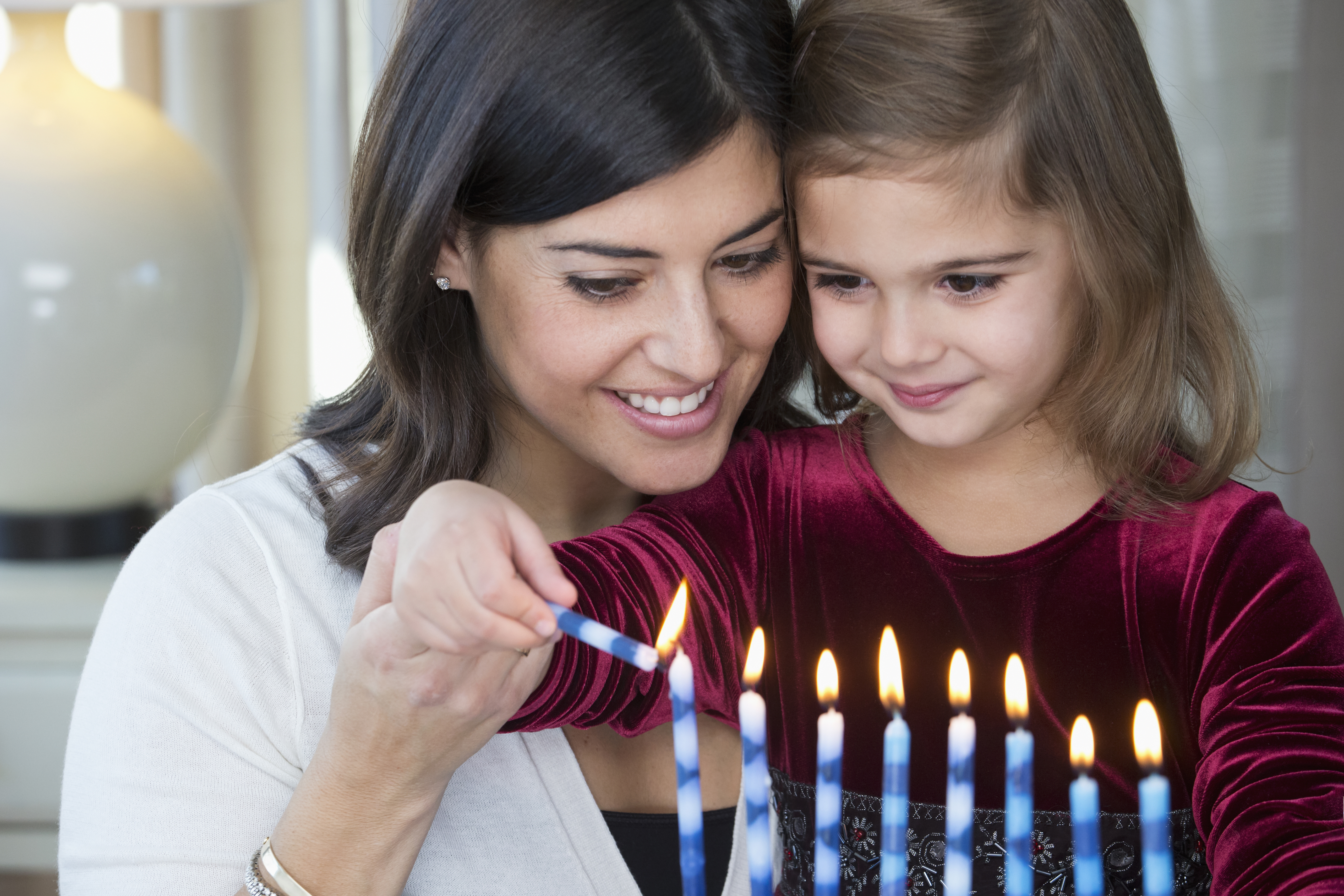 A mother and daughter lighting candles on a Hanukkah menorah. (Getty Images)