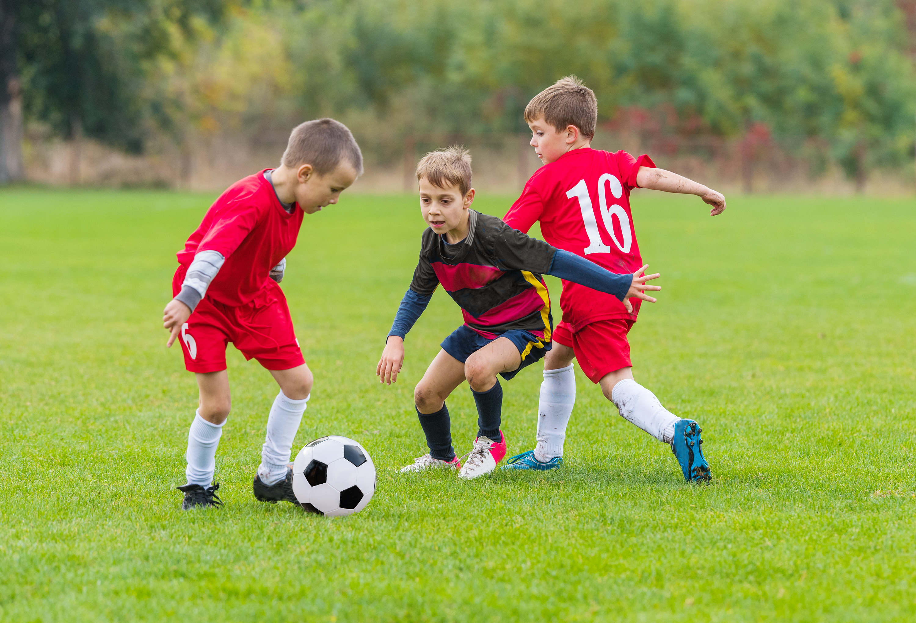 Boys kicking soccer ball on the sports field. (Getty Images)