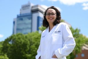 Dr. Jennifer Ozimek stands in front of the tower at UConn Health.