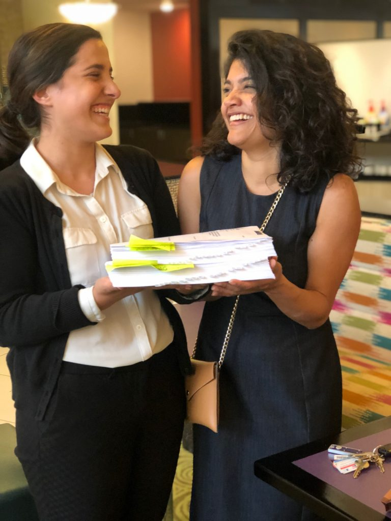 Law student Jenny Labbadia and supervising attorney Valeria Gomez, a teaching fellow with the Asylum and Human Rights Clinic at the UConn School of Law, hold an extensive evidence package that their team developed to support an immigration detainee's asylum claim.