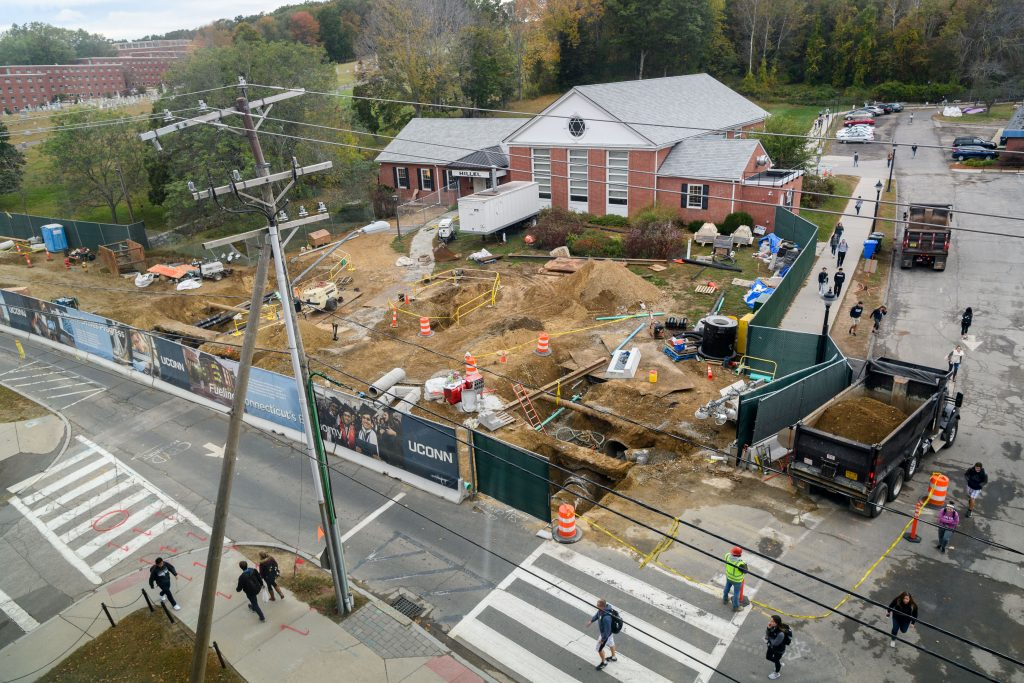 An aerial view of consruction work along North Eagleville Road that shows deep trenches and exposed pipe