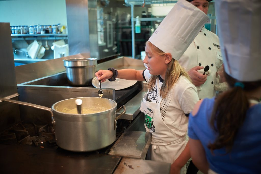 Catie Wigfield, 10, of Baltic, takes a taste of cheese sauce during a competition held at the UCann Cook Camp at Gelfenbien Commons on July 18, 2019. (Peter Morenus/UConn Photo)