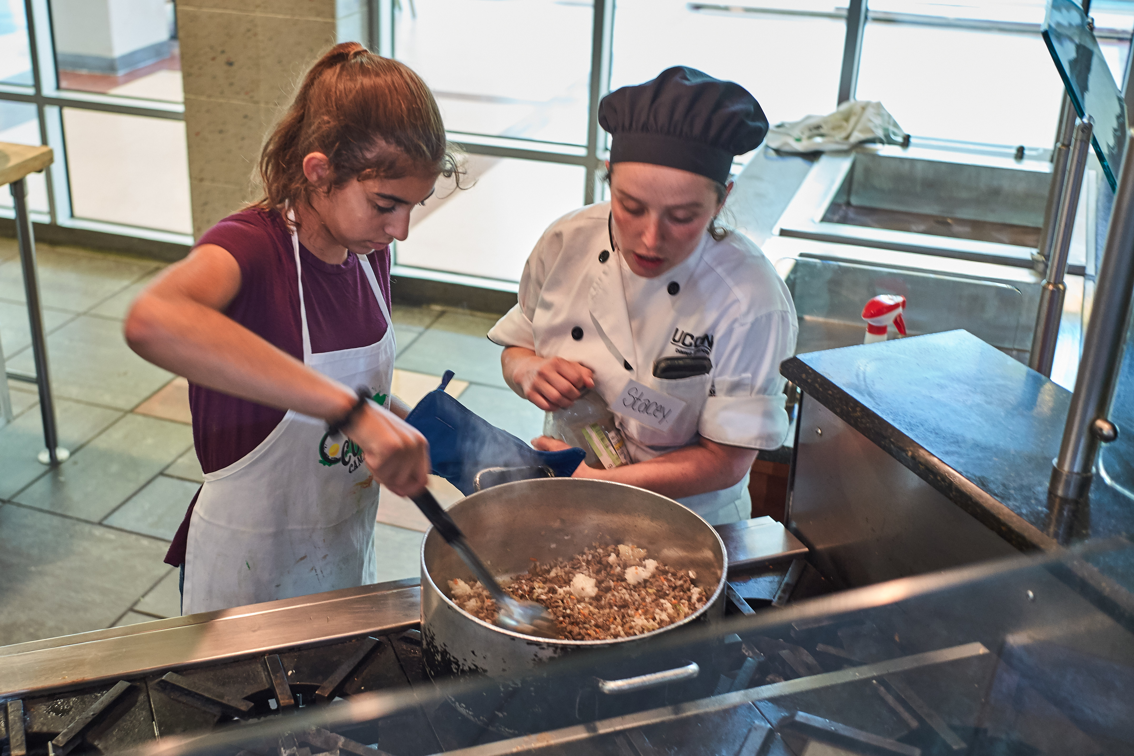 Scarlett Pauloski, 13, of Old Saybrook, left, and Chef Stacy Guitard season taco meat for a main dish during a competition held at the UCann Cook Camp at Gelfenbien Commons on July 18, 2019. (Peter Morenus/UConn Photo)