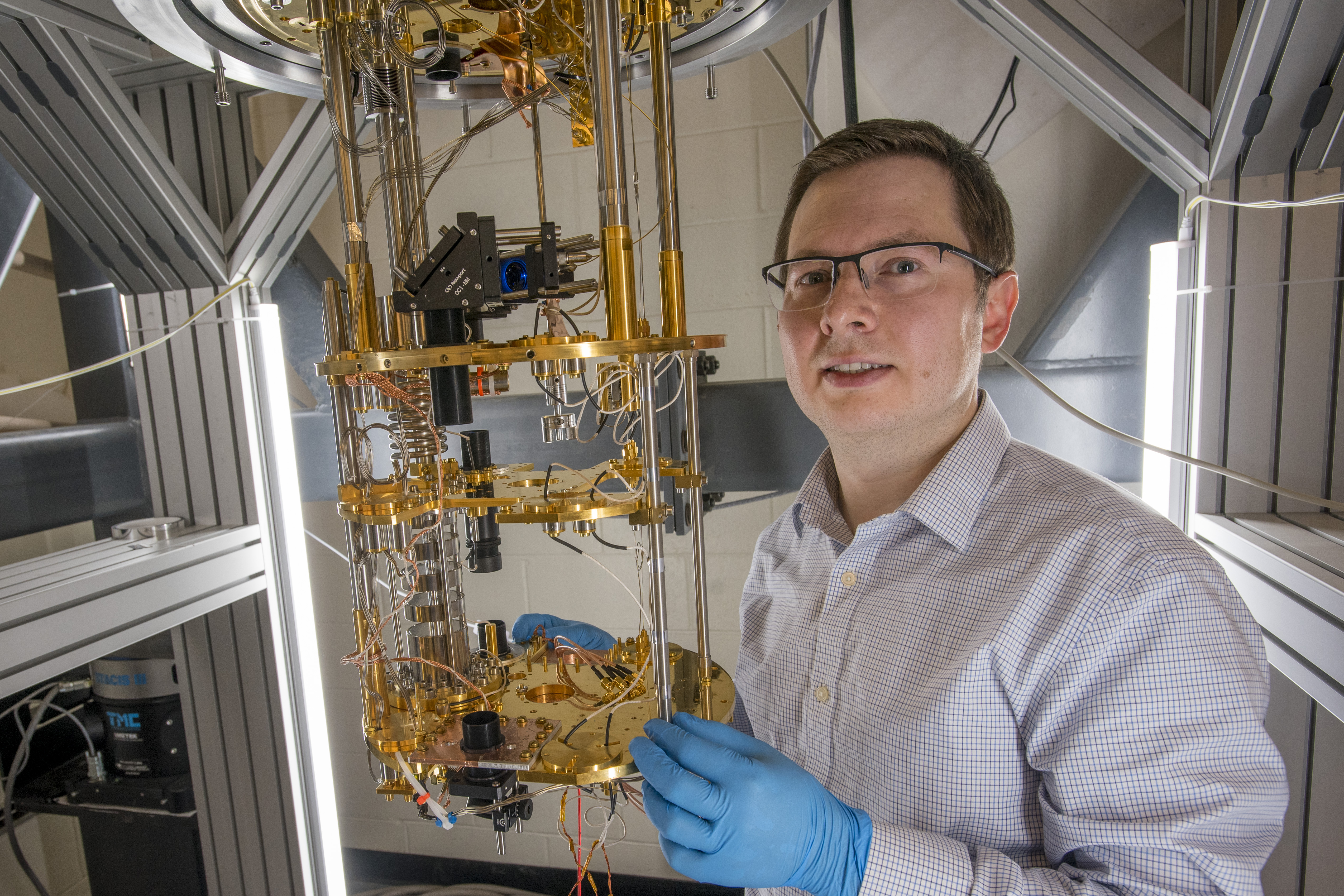 Physics researcher Ilya Sochnikov stands next to a dilution refrigerator in his lab. (Sean Flynn/UConn Photo)