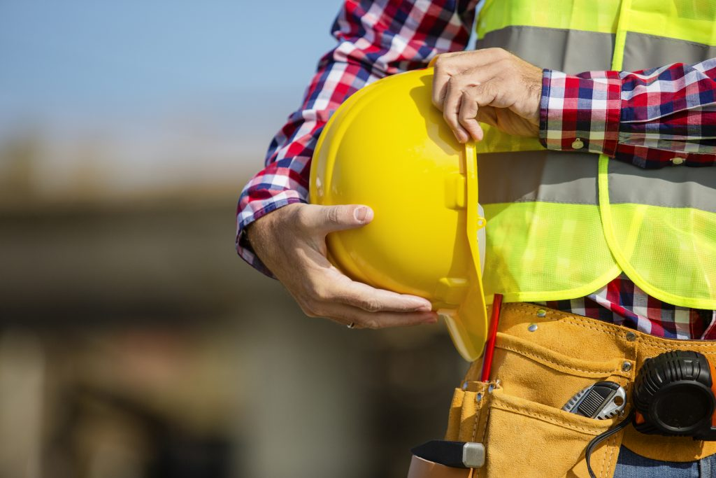 A close-up of a worker holding a yellow hardhat at his side