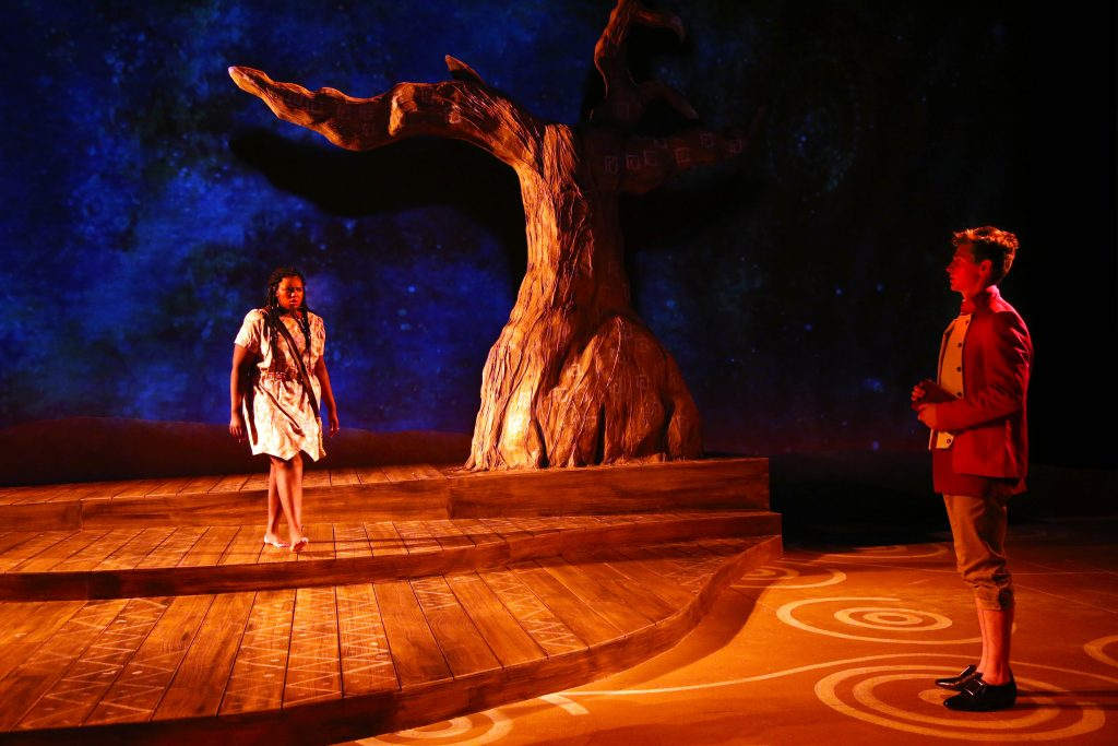 Two actors on stage, an African-American woman and a white man, warily eye each other in a backdrop of Aboriginal Austrlian art and scenery