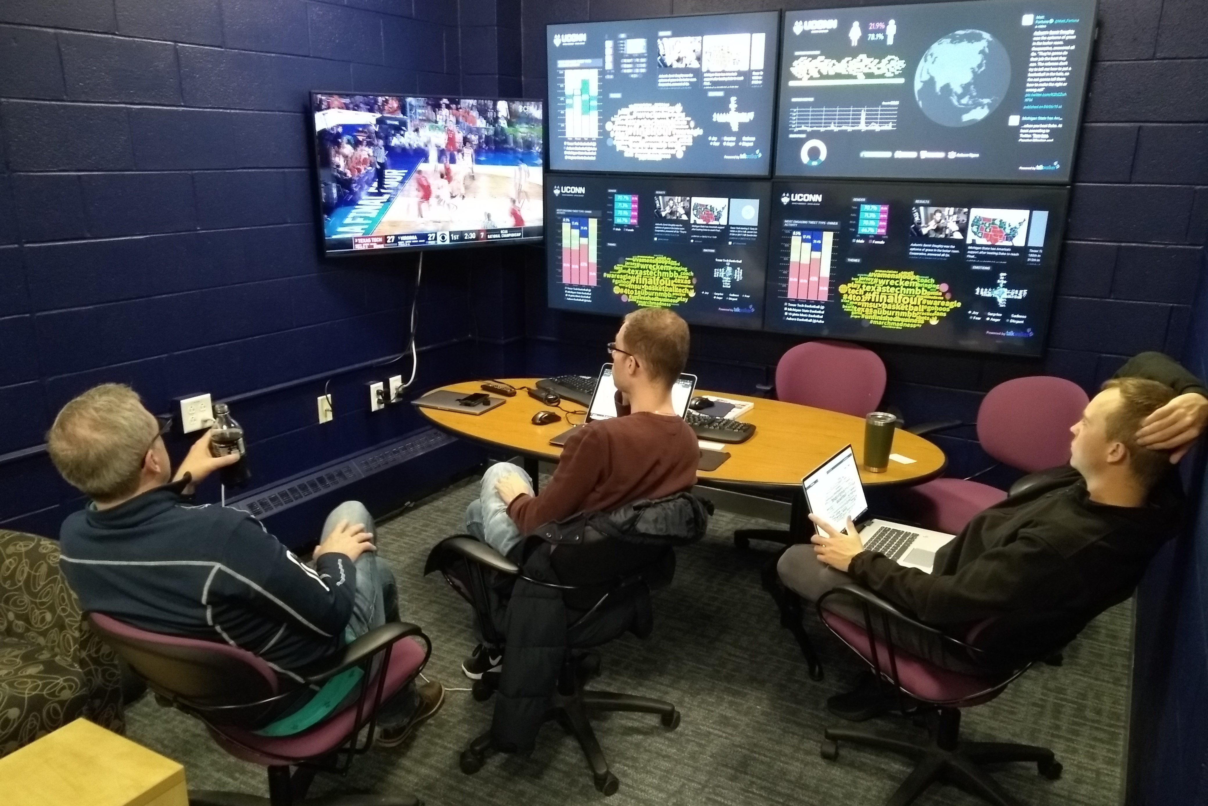 Three men sit in front of a wall full of screens showing a variety of graphics and images relating to social media use during a basketball game.