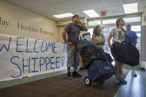 "Four people with bags and boxes standing in the lobby of a dorm, with a handpainted sign behind them reading ""Welcome to Shippee"""