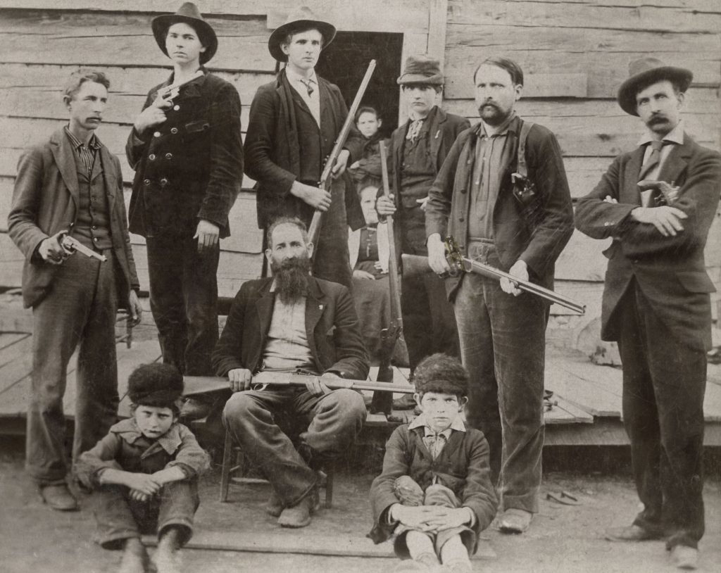 An old photograph shows a group of armed men in front of a rustic cabin