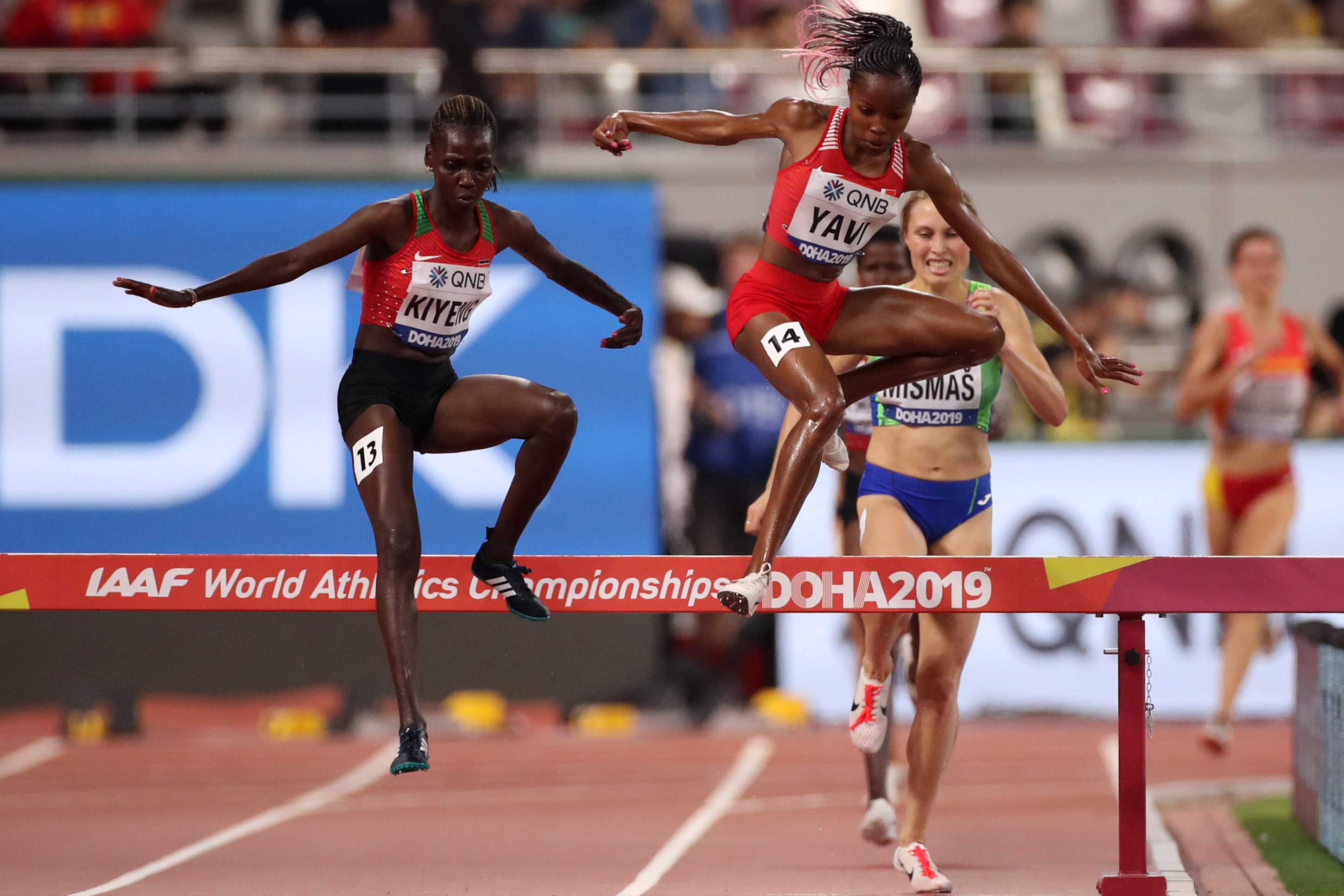Winfred Mutile Yavi of Bahrain (C) and Hyvin Kiyeng of Kenya (L) compete in the Women's 3000 meter Steeplechase heats on Sept. 27, the first day of 17th IAAF World Athletics Championships in Doha, Qatar. (Christian Petersen/Getty Images)
