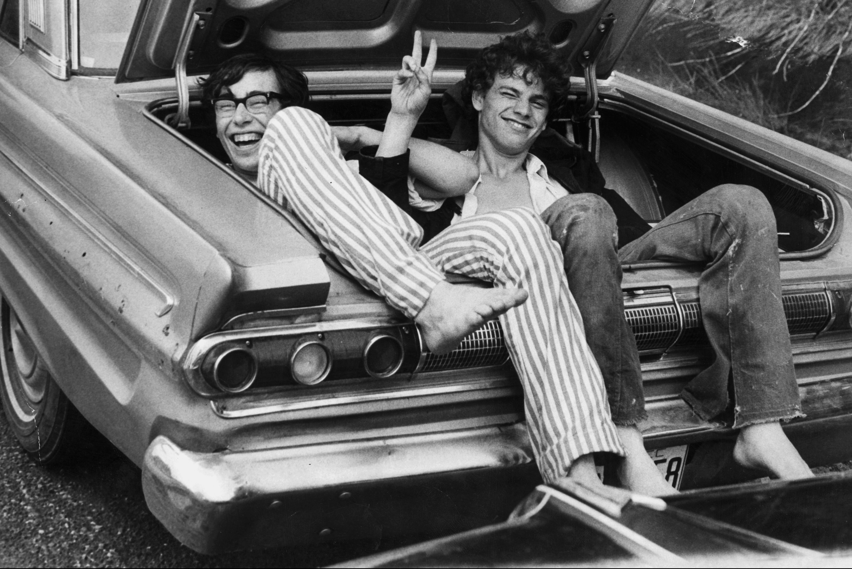 Black and white photo from 1969 of two young men sitting in the trunk of a car, making the peace sign with their hands