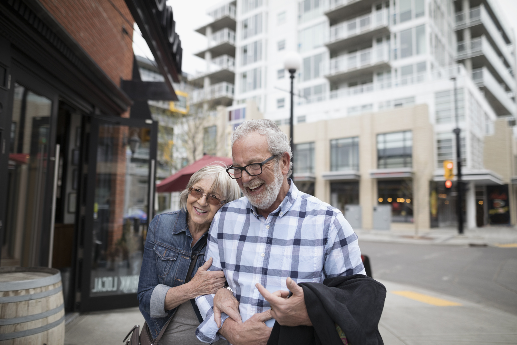 Smiling, affectionate senior couple walking on urban sidewalk