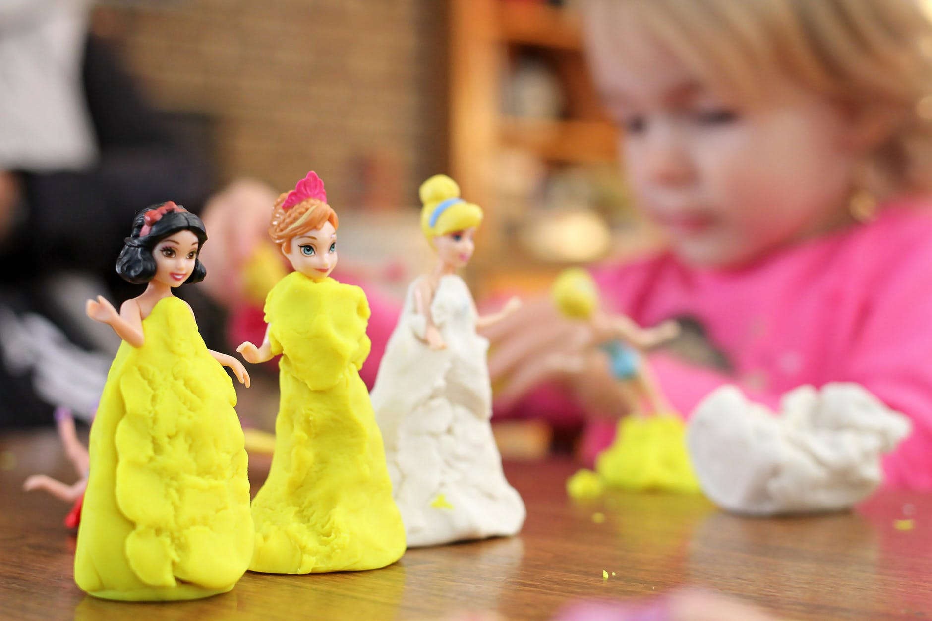 Child molds princess bodies out of clay.