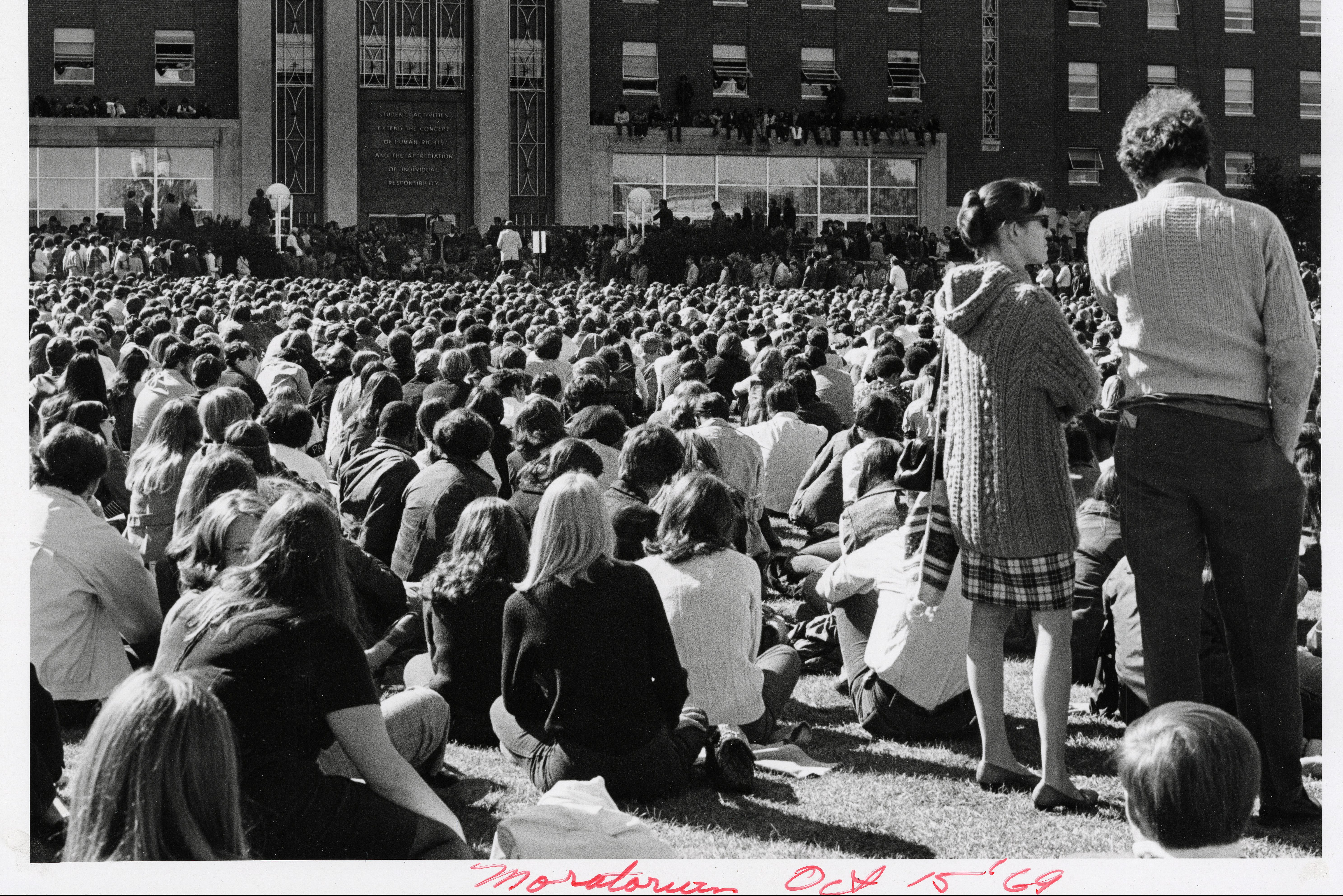 Black and white photo showing a crowd of people listening to speakers in front of the UConn Student Union in 1969