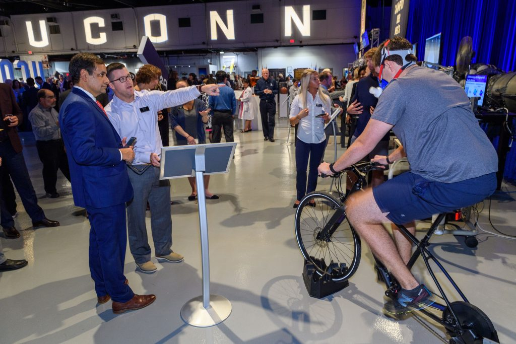 Robert Huggins, center, assistant research professor, explains a Korey Stringer Institute training performance measurement demonstration to Indrajeet Chaubey, CAHNR dean, right. Riding the bicycle is Jeb Struder, a Ph.D. student. (Peter Morenus/UConn Photo)