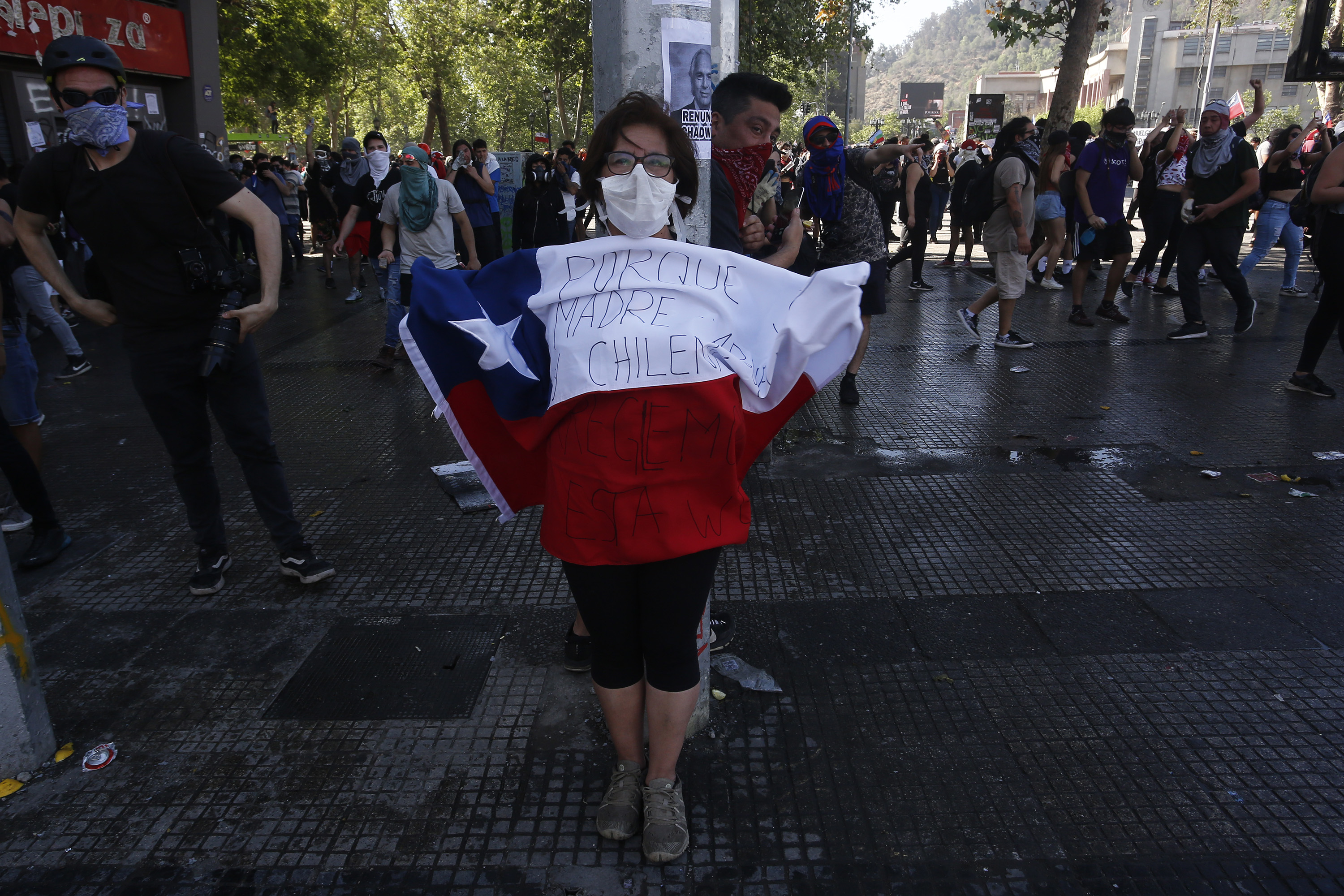 A woman with a comfort mask holds a Chilean flag during a protest in the capital city of Santiago